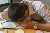 Exhausted man fall asleep on unorganized table with documents, sticky note