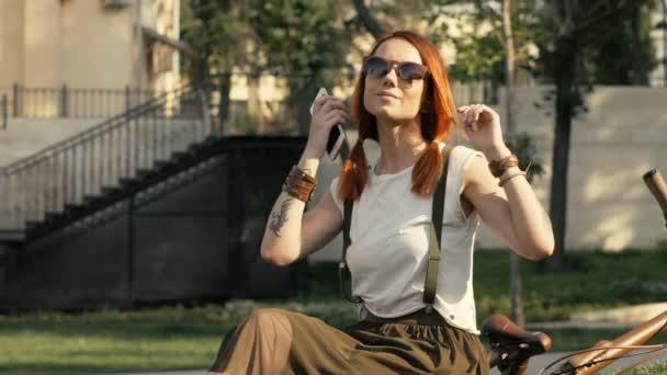 attraktive Radfahrerin mit Sonnenbrille genießt einen sonnigen Tag im Stadtpark