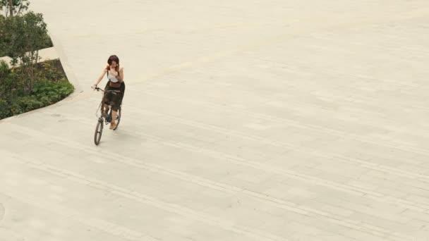 Žena cyklista na kole na zpevněné silnici na náměstí na letní den