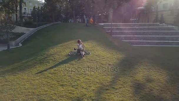 Nő a kerékpáros park zöld füvön feküdt, és mobiltelefon használata