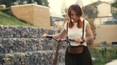 Woman cyclist and bicycle. Woman bike city. Red hair girl and bicycle