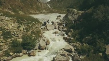 Tourist group crossing the river in mountain. Aerial view mountain river