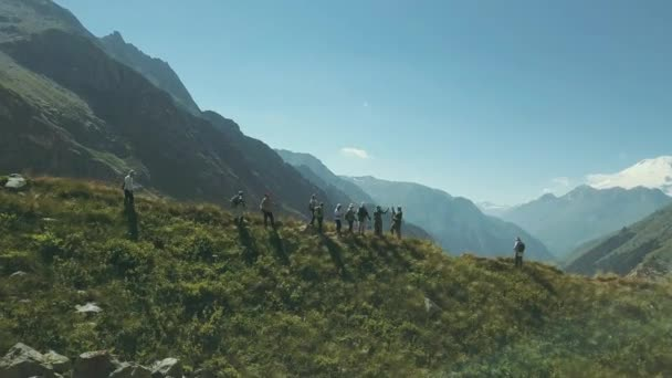 Drone view hiking people standing at mountain edge on background snow peaks