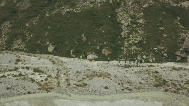 Aerial view tourist group hiking on mountain trail along river. Mountain trip
