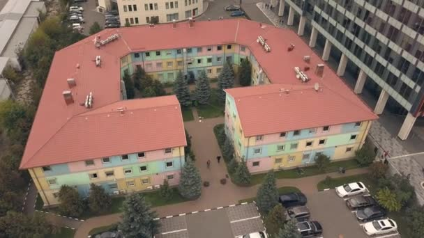 Aerial shooting from flying drone low rise building in business area modern city
