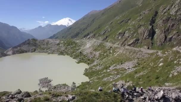 Happy tourist group on mountain edge on background lake and mountain peak