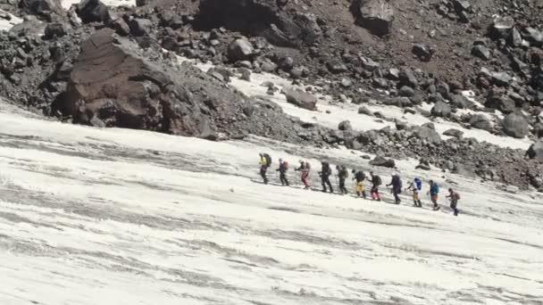 Turistické skupiny chůzi na sněhu v horských údolí. Vrchol hory sněhu.