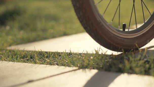 Bicykl, pohybující se na zelené trávě zblízka. Nohy vedle jízdě na kole