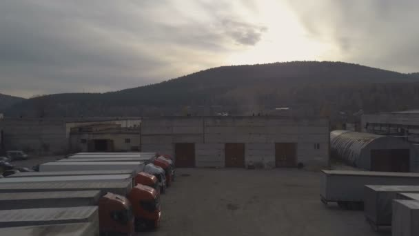 Drone view truck with freight container driving out from parking after unloading