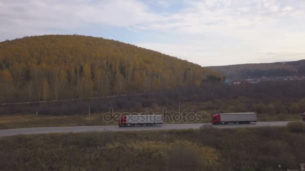 Freight trucks and cars moving on suburban road on background autumn forest