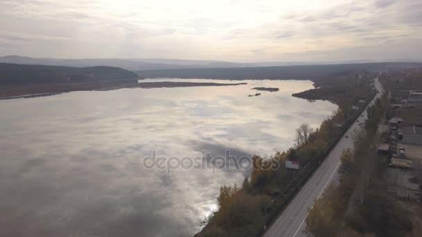 Letecký pohled na kamiony a auta se pohybují na příměstskou silnici na řece pozadí