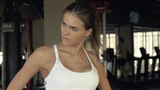 Resto di donna faticosa di forma fisica durante una pausa tra lallenamento di resistenza nel randello di sport