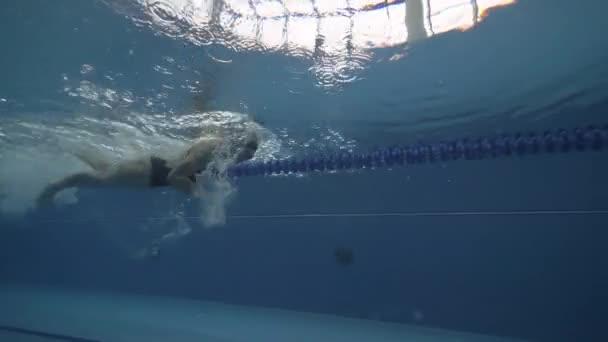 Podvodní pohled žena plovoucí procházení tah na vodě v plaveckých bazén 60 fps