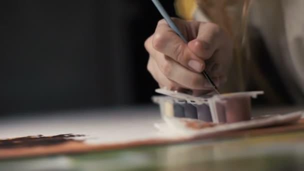 Nő kezek alkotóművész mártással, ecset, festék és ábra rajz