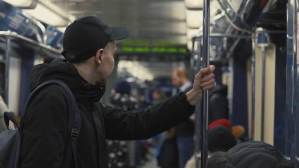 Muž studentský batoh drží madlo během jízdy ve vlaku metra