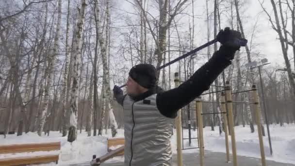 Pohledný muž dělá cvičení cvičení s fitness expandér na sportoviště
