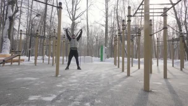 Silný muž dělá squat cvičení s fitness expandér na sportoviště
