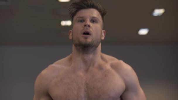 Portrét muže dělá kardio trénink na běžeckém pásu zpomaleně fitness klubu