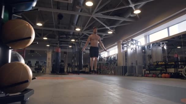 Athlete man doing exercises with skipping rope on crossfit training in club