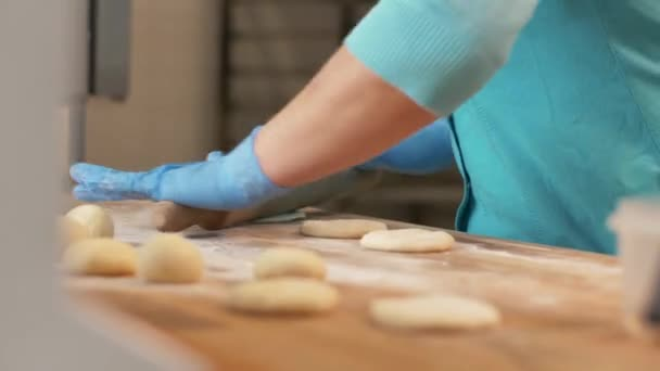 Baker hand rolling dough before baking pastries on table in bakehouse close up