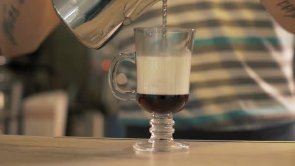 Cafe barista szakadó tej üveg csésze kávé a latte kávézóban előkészítése