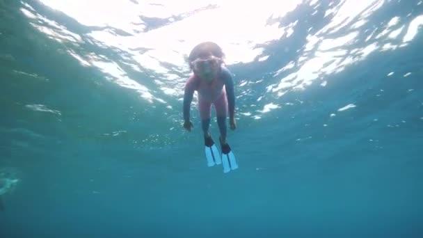 ein tapferes kleines Mädchen, das allein in der blauen Tiefsee schwimmt und taucht.