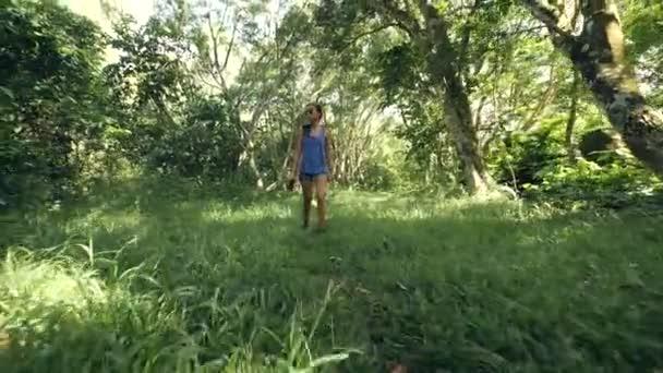 Mladá žena kráčí po zelené stezce v lese plném trávy.
