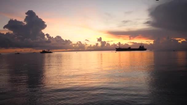 Derűs kilátás hajnalra a tengerben sötét felhőkkel, narancssárga égbolttal és vízzel.