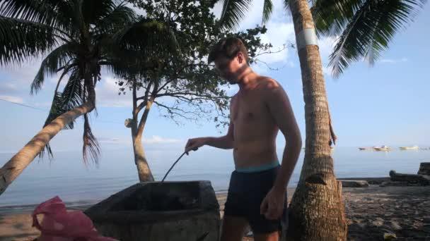 Mann bereitet an einem sonnigen Tag am Strand kurz Holzkohle zum Grillen vor