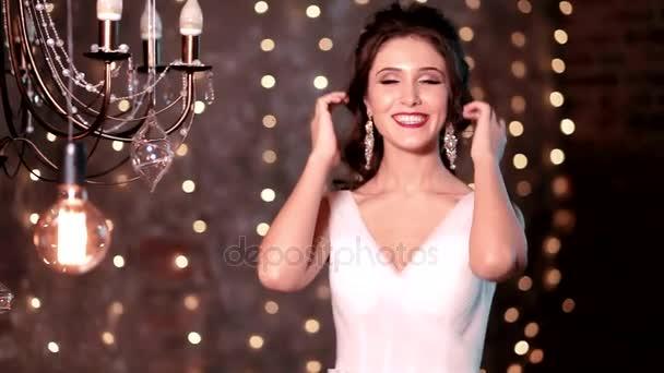 šťastné krásné sexy nevěsta brunetka žena v bílé svatební šaty s účes a světlý make-up v interiéru