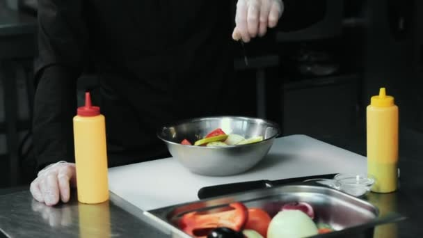 Köche salzen in der Restaurantküche mit der Hand.