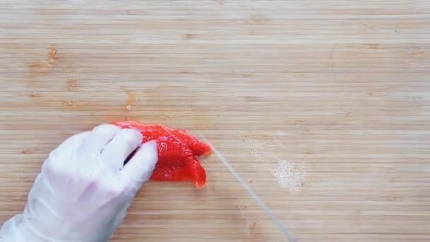 Chef slicing a red bell pepper on a wooden cutting board. Top view.