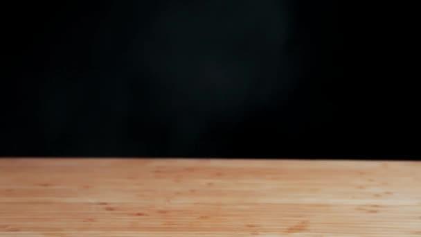 Clouse jídlo. Připravené ražniči špíz. Ruku otočí šíš kebab na jehle na dřevěný stůl. Černé pozadí
