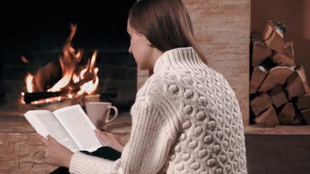 A lány hátradől és könyvet olvas otthon.