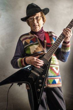 old woman playing electric guitar