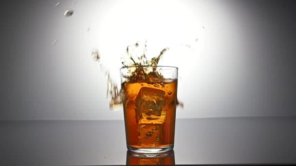 Eiswürfel fällt ins Glas