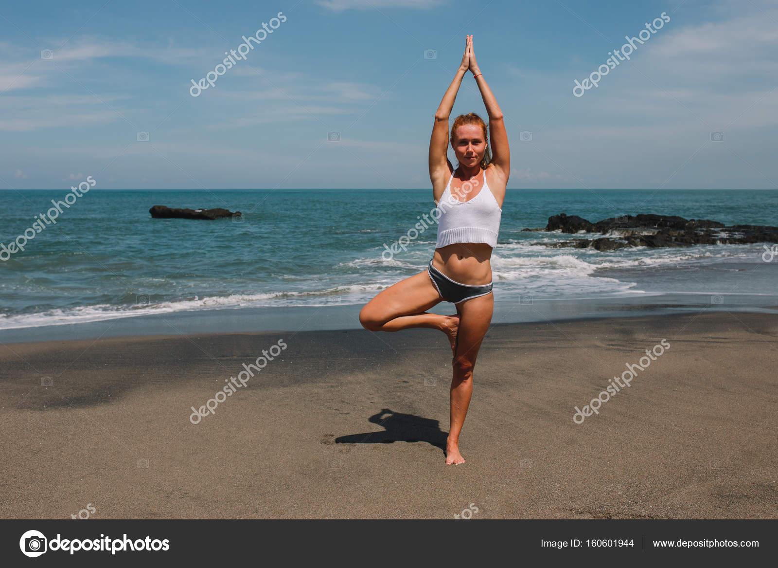 Giovane ragazza capelli rossi praticare yoga sulla ...