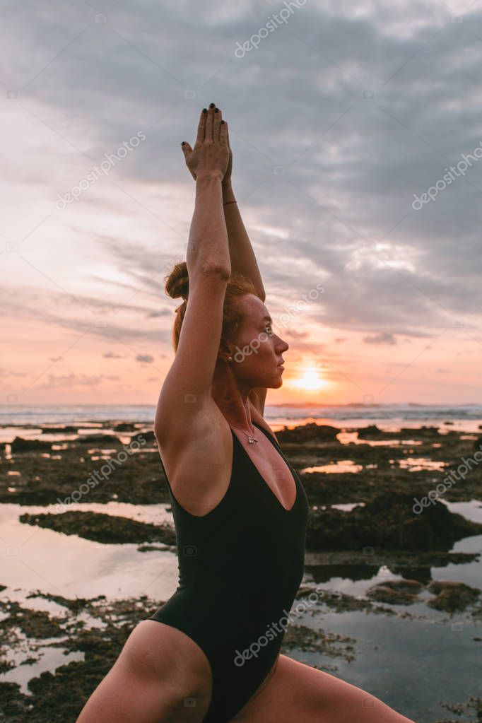 Young attractive girl practicing yoga on the beach during sunset