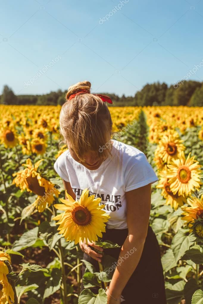 happy young woman enjoying summer at sunflower field