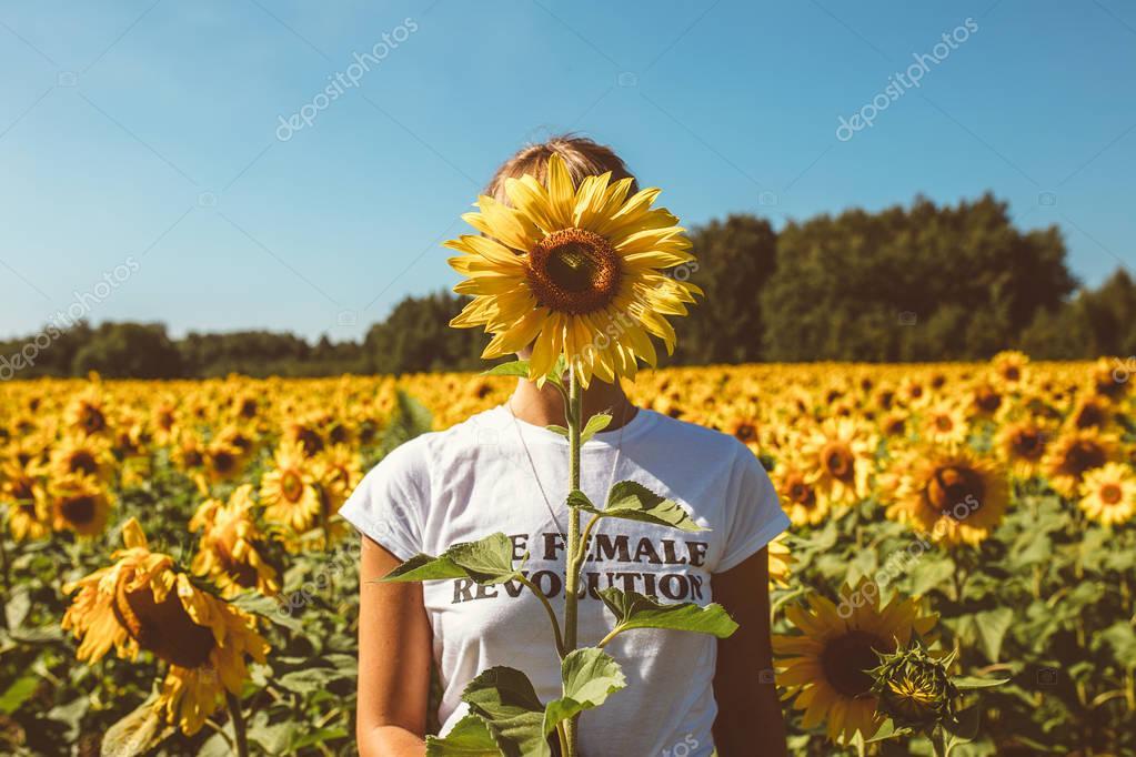 Beautiful stylish hippie girl on the sunflower field