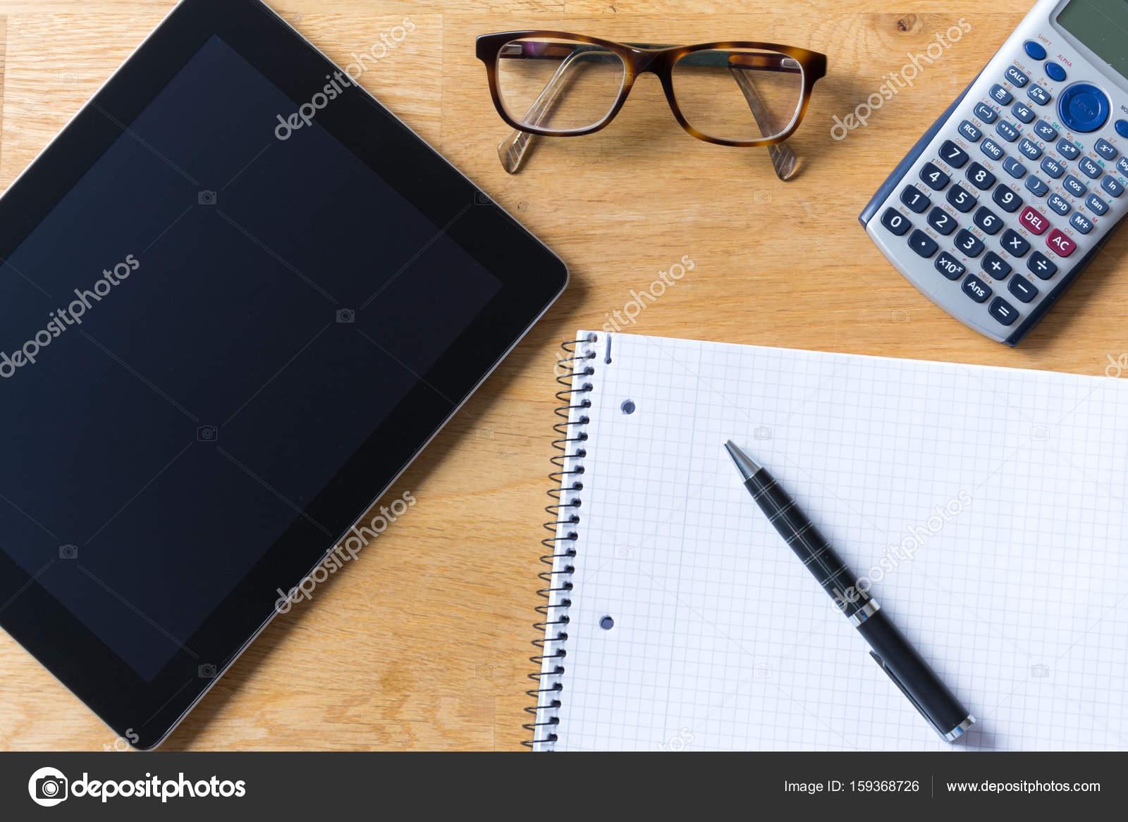 Bureau avec tablette verres calculatrice et bloc notes sur bois