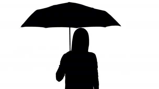 Siluetta di una donna che tiene un ombrello