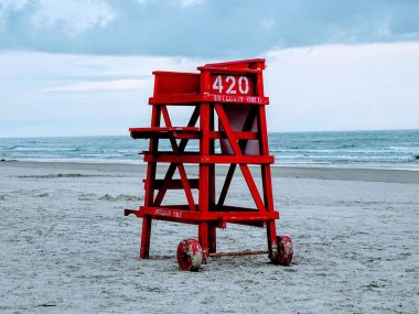 Red lifeguard stand on a deserted beach.