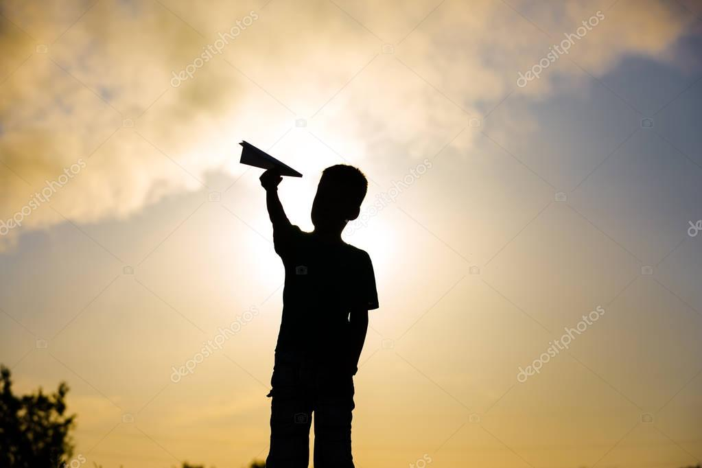 A happy child is playing with a paper airplane at sunset. Classes with children outdoors. Life style