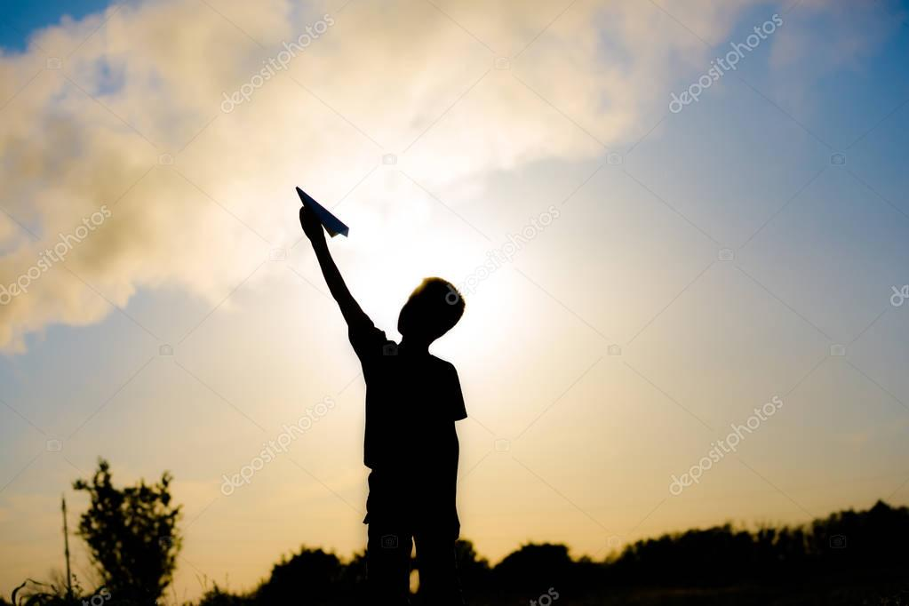 A happy child is playing with a paper airplane at sunset. Classes with children outdoors. Lifestyle