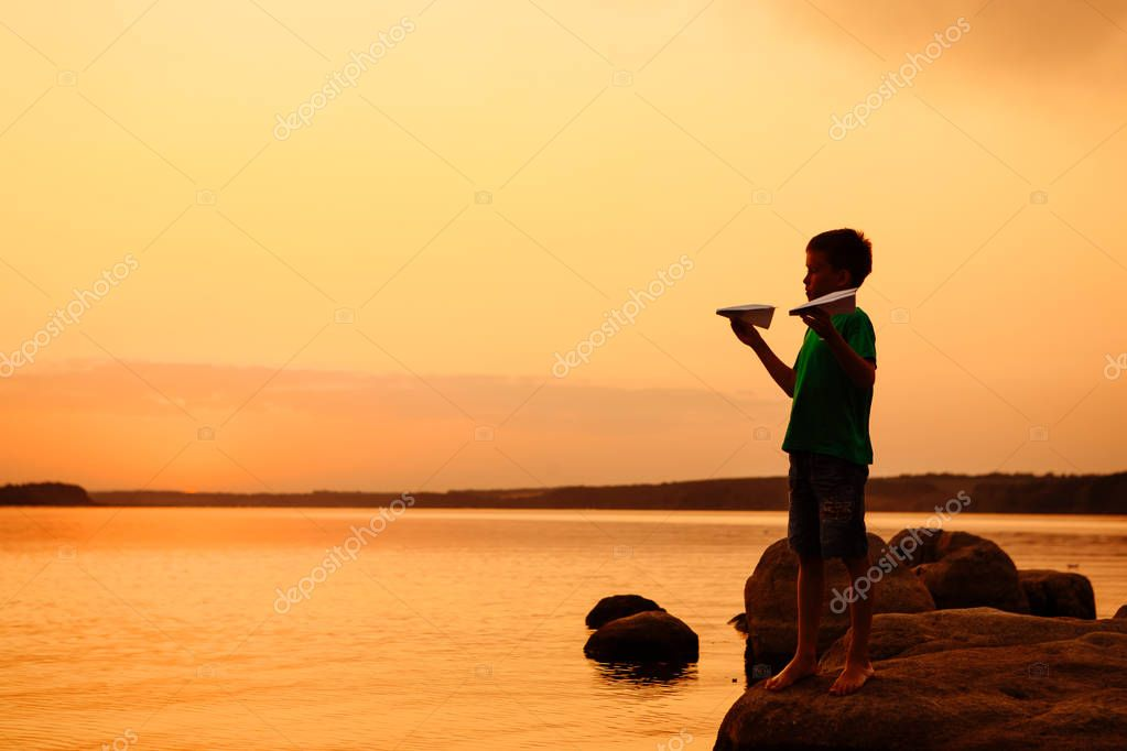 Happy child playing with paper airplane on background of river. Beautiful summer sunset. Classes with children outdoors. Life style