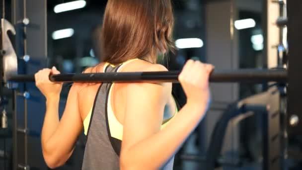 Pohled zezadu na silná mladá žena dělá sit-up během intenzivně zacvičit v moderní posilovně. Detail