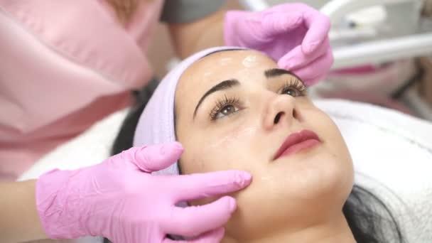 Bella giovane ragazza ottenere un trattamento viso procedura di pulizia da un cosmetologo. Massaggio rigenerante. Centro benessere