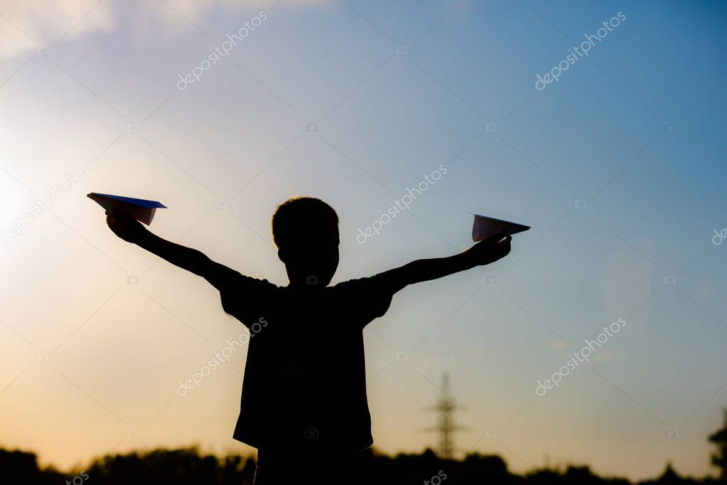 Happy child is playing with a paper airplane at sunset. Classes with children outdoors. Lifestyle