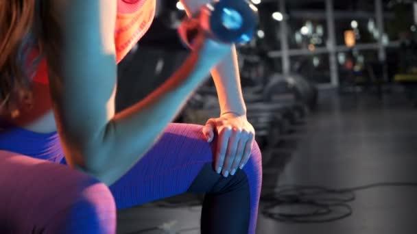 Nádherné fitness žena zvedání činek. Sportovní dívka ukazuje její tělo dobře trénovaní. Posilovna a fitness